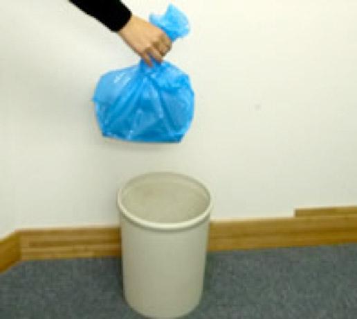 袋の口を閉じた排便収納袋をゴミ箱に入れる